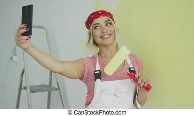 Cheerful female taking selfie with paint roller - Happy...