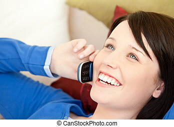 Cheerful female teenager talking on phone lying on a sofa in...