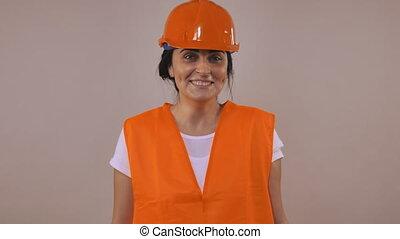 happy beautiful caucasian woman with black hair wearing hard hat and orange uniform posing in studio. Portrait young girl wearing casual white t-shirt