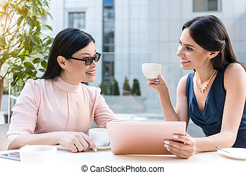 Cheerful females speaking at desk in cafe