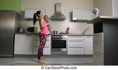 Cheerful fit mom doing squats with baby at home