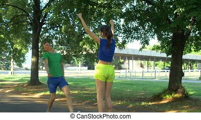 Cheerful fit woman encouraging runner outdoors