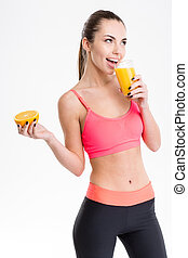 Cheerful fitness girl drinking juice and holding half of...