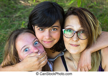 Cheerful foolish portrait, mom with her two daughters.