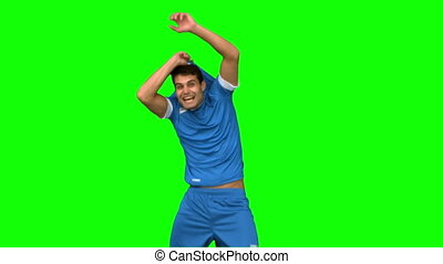 Cheerful football player celebrating a goal on green screen...