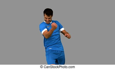 Cheerful football player gesturing on grey screen in slow...
