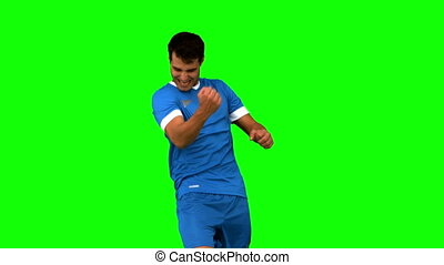 Cheerful football player gesturing on green screen in slow...