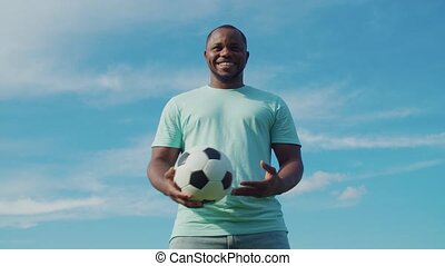 Cheerful handsome black football player in casual clothes holding and juggling soccer ball outdoors, looking with friendly smile, expressing positivity and good vibes over blue sky in background.