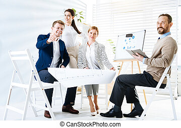 Cheerful four  colleagues deciding on business plan