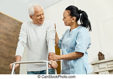 Cheerful friendly nurse helping the elderly man
