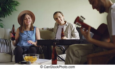 Cheerful friends are having fun talking, singing and drinking beer during rehearsal. Guitarist is playing, woman and man are clanging bottles and laughing.