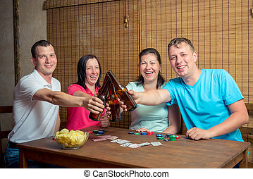 cheerful friends drink beer for card game indoors