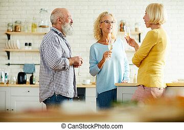 Cheerful friends drinking champagne in kitchen