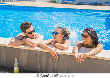 cheerful friends drinking cocktails in the pool