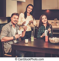 Cheerful friends eating fast food in home interior