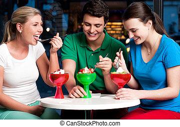 Cheerful friends enjoying tempting dessert