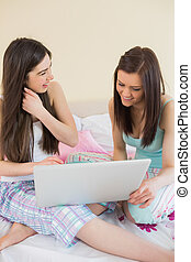 Cheerful friends in pajamas talking on bed using a laptop