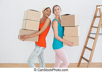 Cheerful friends moving together in a new house
