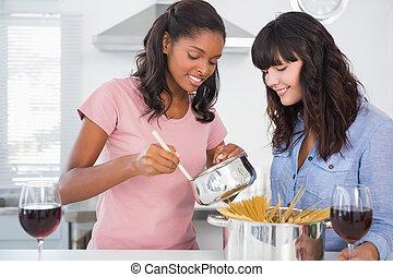 Cheerful friends preparing spaghetti dinner together
