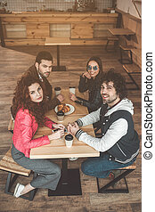 Cheerful friends relaxing in cafe together