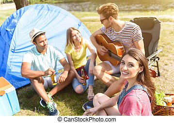 Cheerful friends relaxing in forest