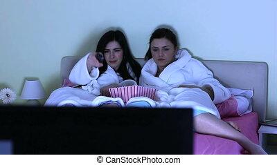 Cheerful friends watching movie