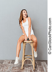 Cheerful funny woman sitting on the chair