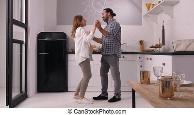 Happy attractive couple expecting baby enjoying dance and conversate in cozy kitchen. Smiling husband with pregnant wife dancing holding hands while spending family leisure together at home