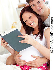 cheerful future parents reading a book sitting on their bed during the morning at home