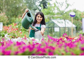 Cheerful gardener watering plants outside in garden center