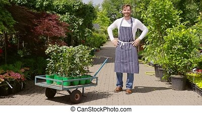 Cheerful gardener with wagon - Horizontal outdoors shot of...