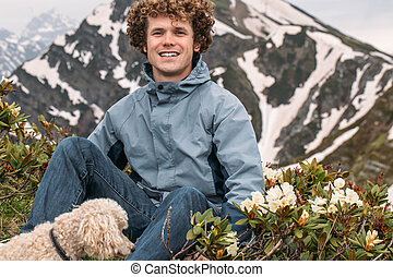 cheerful ginger touris sitting near the fowers and pedigree dog on landscape