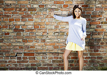 Cheerful girl against a brick wall