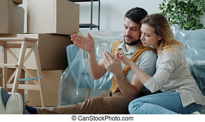 Cheerful girl and guy are using smartphone touching screen and pointing at interior of new apartment looking for ideas online. People and relocation concept.