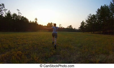 Cheerful girl, arms raised running across the field at sunset