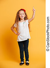 Cheerful girl child standing isolated pointing