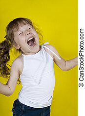 Cheerful girl dances on a yellow background