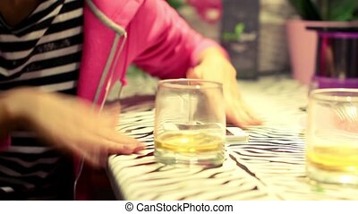 cheerful girl drinking alcohol and bangs her hand on the bar to the music