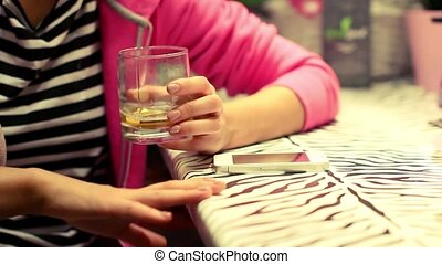 cheerful girl drinking alcohol and bangs his hand on the bar to the music