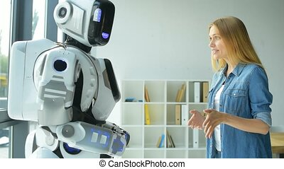 Cheerful girl gesturing while talking with robot