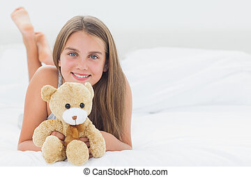 Cheerful girl holding a teddy bear