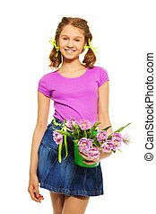 Cheerful girl holding pail with pink tulips