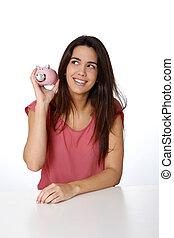 Cheerful girl holding piggy bank