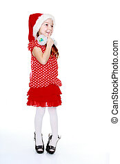 Cheerful girl in a polka dot dress and hat of Santa Claus