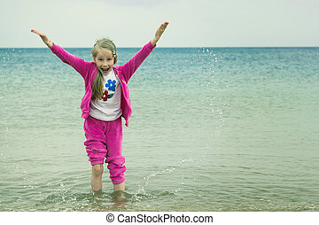 Cheerful girl in a warm suit plays with water in a cold sea.