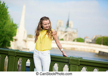 Cheerful girl in Paris with Notre-Dame behind her