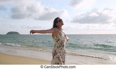 cheerful long haired girl in short summer sundress walks along empty beach near azure ocean water on windy day