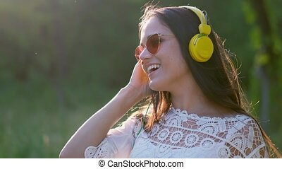 Girl In Sunglasses And Large Yellow Headphones Listens To...