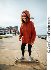 cheerful girl in the orange hoodie rides on street on a...