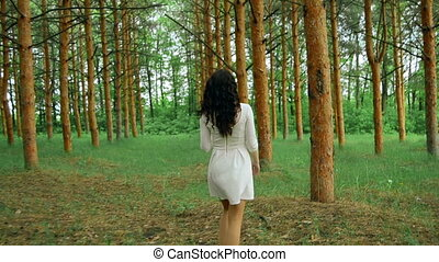 cheerful girl in white dress walks in the forest